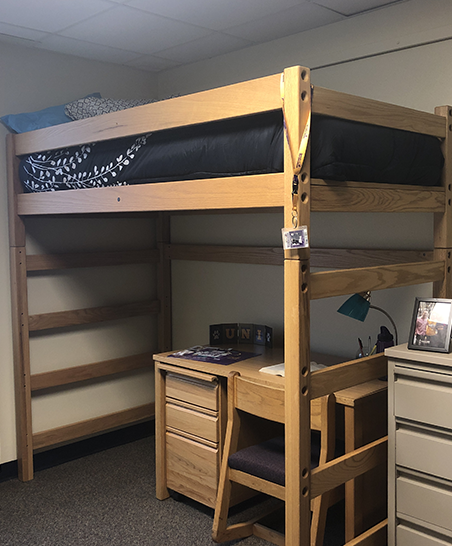 Bed lofted with futon situated underneath, micro-fridge adjacent