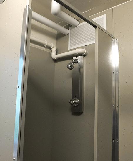 Community bathroom view of shower stalls