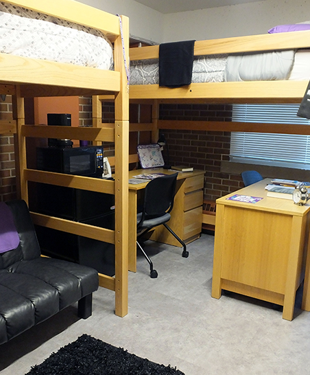 Beds lofted with desks and futon situated underneath.